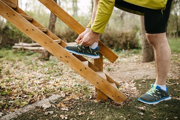 나무 계단 배경에 운동화에 구두 끈을 묶는 러너의 근접