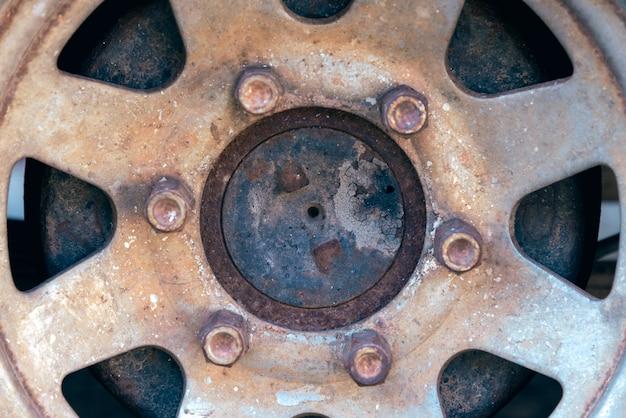 放棄された車のさびたホイールキャップのクローズアップ。