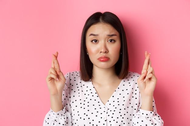 悲しくて希望に満ちたアジアの女性のクローズアップは、願い事をし、幸運とふくれっ面を交差させ、動揺して、ピンクの上に立っています