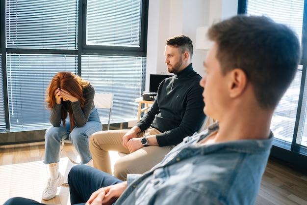 그룹 치료 세션 동안 원에 앉아 문제를 공유하는 슬픈 우는 젊은 여성의 클로즈업. 우울한 빨간 머리 여성이 사무실에서 다른 환자들에게 정신적 문제에 대해 이야기합니다.