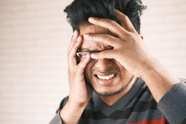 Крупным планом грустный человек, закрывающий лицо рукой