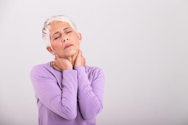 Закройте вверх унылой старшей дамы с болью в шее. пожилая женщина с хроническим болевым синдромом фибромиалгии страдает острыми шейными болями.