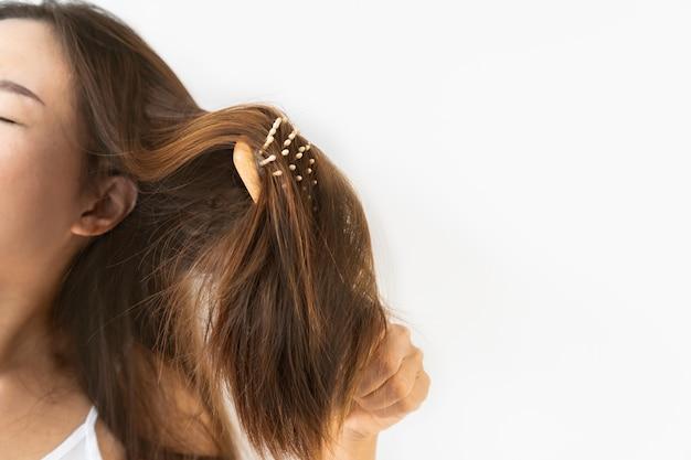 슬픈 젊은 아시아 여자 브러시 그녀의 손상 및 얽힌 머리 닫습니다. 복사 공간 흰 벽에 절연