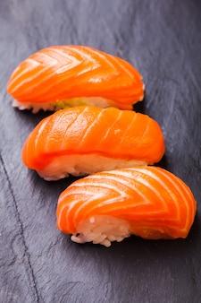 Крупный план суши саке с лососем на фоне черного сланца