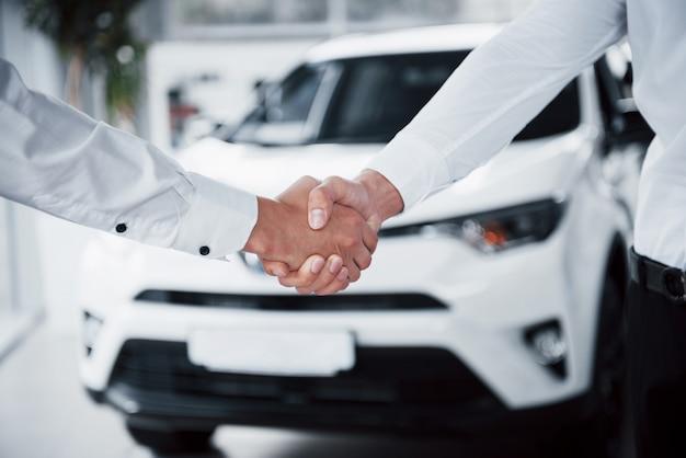 顧客に車を販売する黒いスーツのセールスマネージャーのクローズアップ