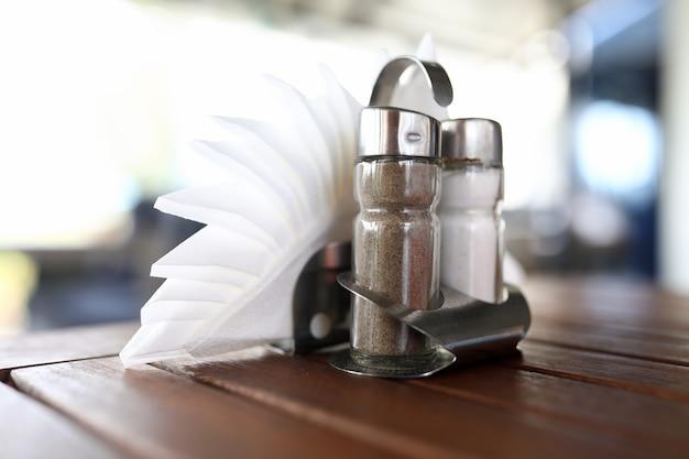 塩とコショウのシェーカーとテーブルの上に横になっているスタンドのナプキンのクローズアップ。木製の机の上に立っているスパイスのガラス容器。カフェとレストランのコンセプト