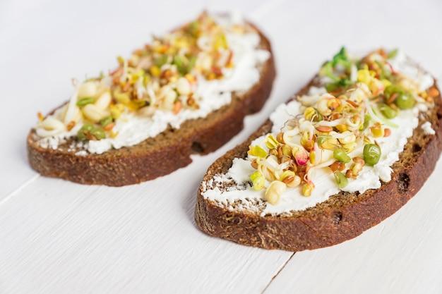 Закройте бутерброды на ржаной хлеб с сыром и проросшими бобы мунг, грецкий орех, подсолнечник и лен. макробиотический здоровый завтрак.