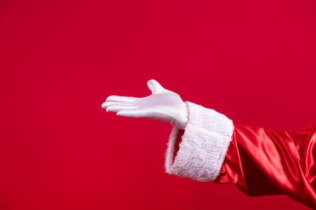 빨간 배경에 몸짓을 주는 산타클로스 장갑을 낀 손 쇼의 클로즈업. 새해 복 많이 받으세요, 메리 크리스마스, 전통적인 계절 축하를 위한 축제 시간.