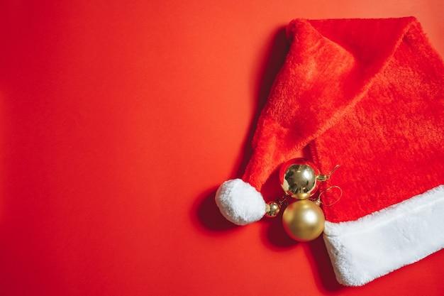 赤い背景の上のサンタ帽子とクリスマスツリーの装飾のクローズアップ。スペースをコピーします。
