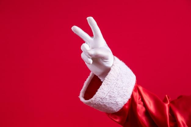 빨간색 배경에 v 표시를 만드는 산타의 장갑을 낀 손의 클로즈업.