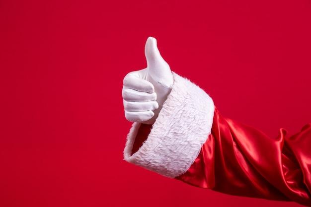 빨간색 배경에 확인 표시를 만드는 엄지손가락으로 산타의 장갑을 낀 손의 클로즈업. 새해 복 많이 받으세요 축제 시간, 메리 크리스마스, 전통적인 계절 축하.