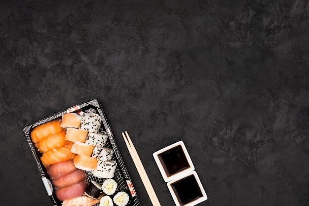 검은 표면 위에 간장 소스와 함께 접시에 생선 초밥의 근접