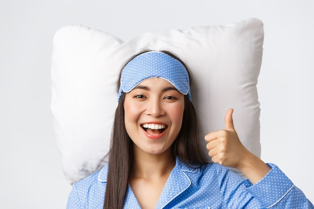 파란색 잠옷과 수면 마스크를 쓴 만족스러운 아시아 소녀의 클로즈업, 부드러운 편안한 베개에 침대에 누워, 승인에 엄지손가락을 보여주는 것, 제품 또는 불면증 약 추천