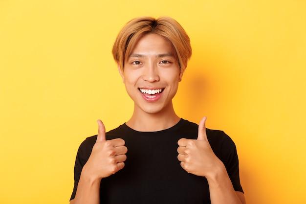 Крупный план довольного, счастливого азиатского парня в черной футболке, одобрительно показывая большие пальцы руки вверх, улыбаясь и соглашаясь, стоящего на желтой стене.