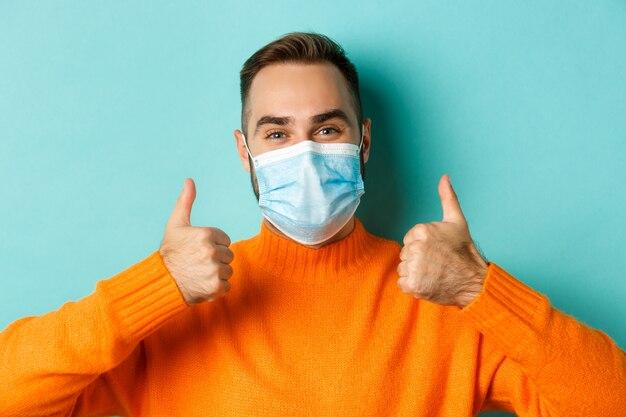 親指を立てて、賞賛し、同意し、立っていることを示す医療マスクの満足している男性モデルのクローズアップ