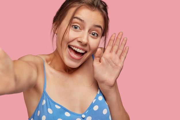 만족 한 여자의 클로즈업은 셀카 또는 화상 통화, 파도를 만들고 즐거운 표현을 가지고 있습니다.