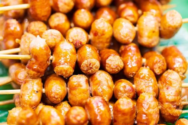 タイの伝統的なスタイルのソーセージ焼き、サイクロークイーサーン、豚肉とご飯、タイの屋台の食べ物の市場のクローズアップ