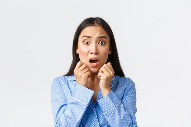 Крупный план испуганной азиатской женщины в панике, стоящей в пижаме, потерявшей дар речи, реагирующей на пугающую и шокирующую сцену, выглядящей испуганной, дрожащей от страха на белом фоне.