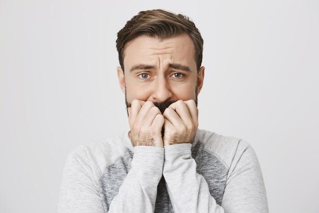 Крупный план испуганного бородатого парня, выглядящего встревоженным и встревоженным