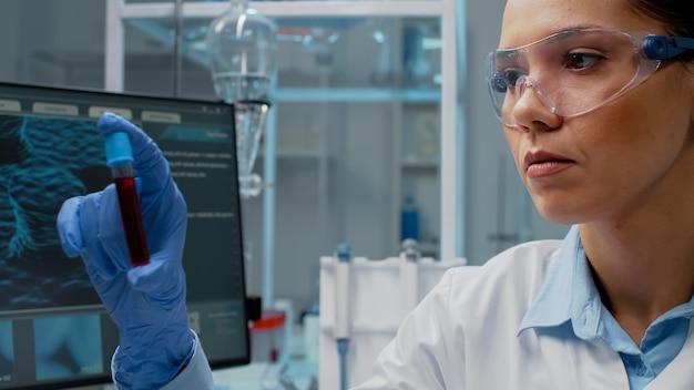 액체로 실험실 vacutainer를 분석하는 과학자의 클로즈업