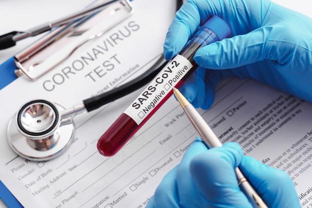 Sars-cov-2의 혈액 샘플을 가진 과학자 손 클로즈업