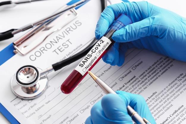 Sars-cov-2 の血液サンプルを使用した科学者の手のクローズ アップ