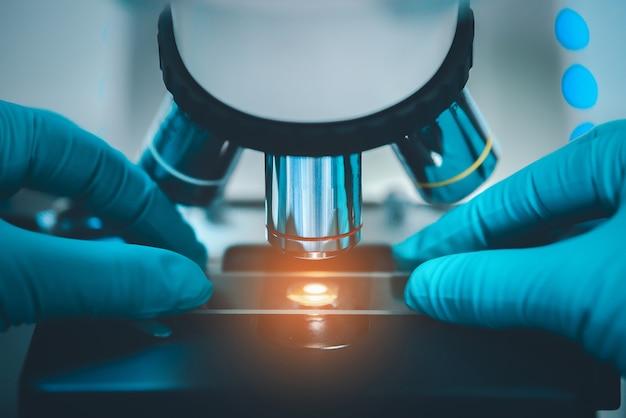 Закройте руки ученого с микроскопом в медицинской исследовательской лаборатории или научной лаборатории.