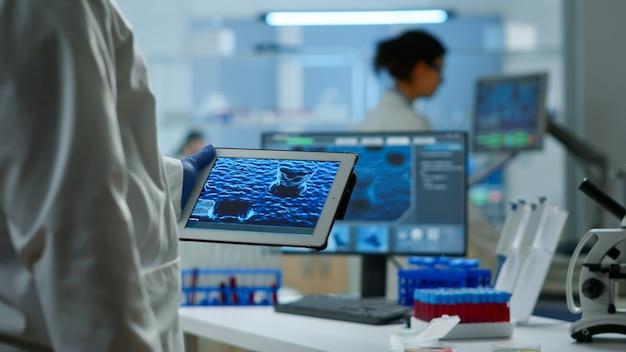 Закройте ученого в лабораторном халате, работающем с таблеткой, стоящей в современной оборудованной лаборатории. команда химиков изучает эволюцию вакцины, используя высокотехнологичные и химические инструменты для разработки вирусов.