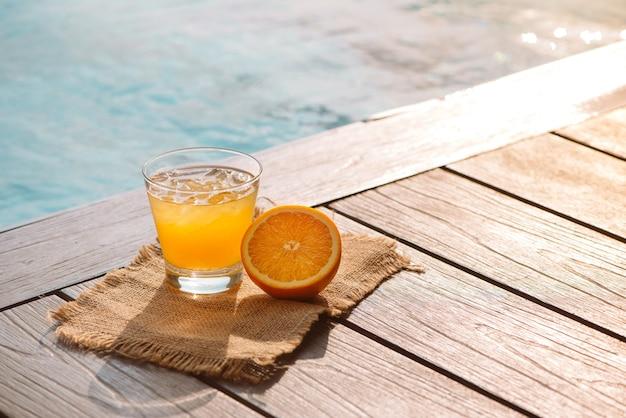 수영장 근처에 서 있는 오렌지 주스, 조각, 얼음과 함께 드라이버 칵테일 알코올 음료를 닫습니다. 수영장 옆 유리에 있는 상쾌한 아이스 레모네이드 음료. 태양 눈부심. 배경, 복사 공간입니다.