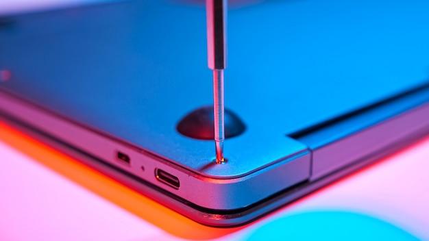 赤青の光の中でラップトップカバーにボルトをねじ込むクローズアップ。
