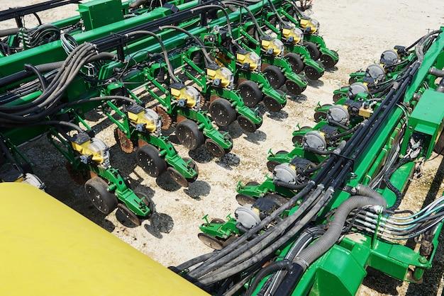 Закройте сеялку, прикрепленную к трактору в поле.