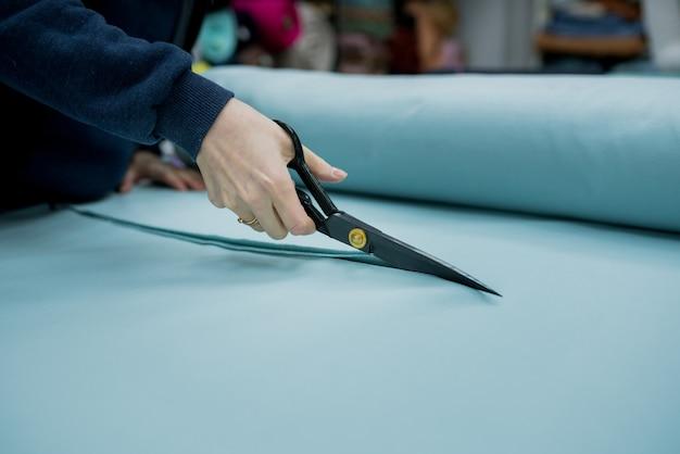 Крупным планом продавец, резающий ткани в текстильном магазине, швея, используя ножницы, чтобы обрезать материал