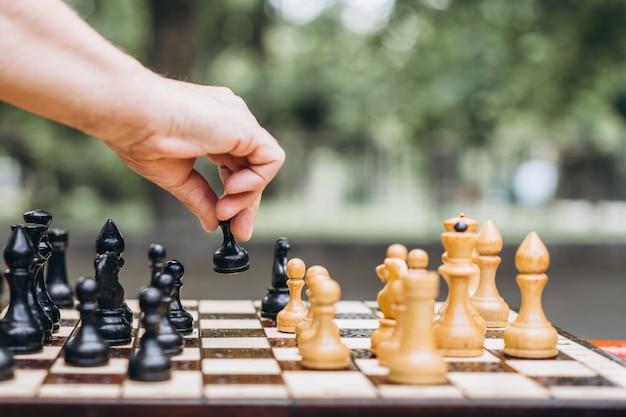 公園の屋外のベンチでチェスをするシニア成人男性の手のクローズアップ。