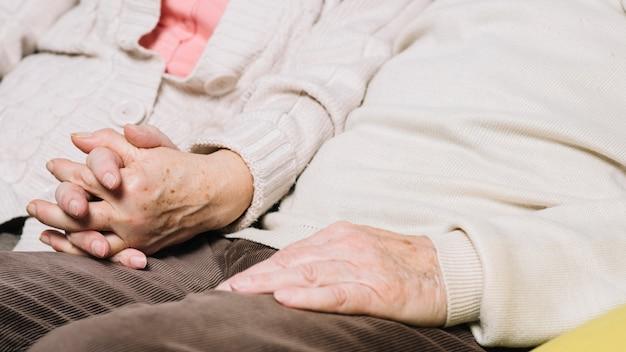 Крупным планом пожилые супружеские пары, взявшись за руки Бесплатные Фотографии