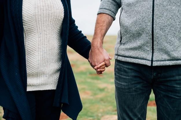 手をつないでいる年配のカップルのクローズアップ