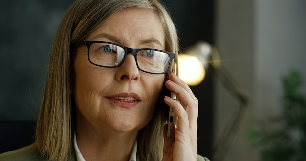 彼女のオフィスでのビジネスについての携帯電話で話しているガラスのシニアの格好良い女性のクローズアップ。