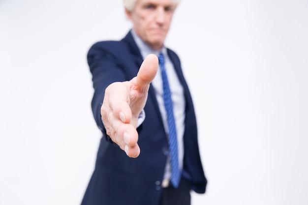 Крупным планом старшего руки продлен для рукопожатия