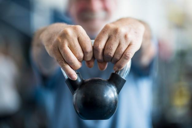 ジムでカメラの前で両手で体重を保持している先輩のクローズアップ-健康のために彼の体を働いている成人男性