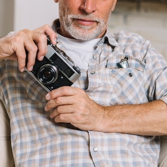 Close-up of senior man holding camera in hand