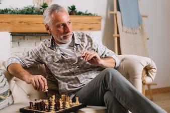 Close-up of senior man sitting on sofa playing chess
