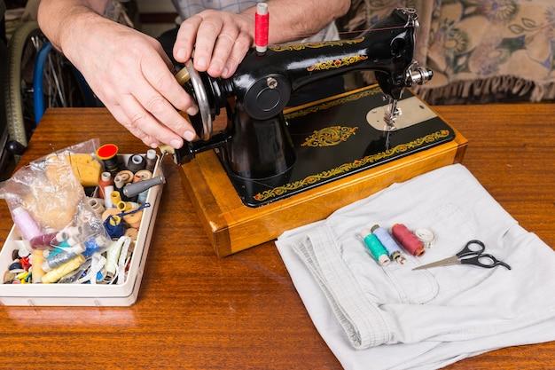 Крупным планом старший мужчина, использующий старомодную ручную швейную машину, в окружении швейных материалов и различных ниток