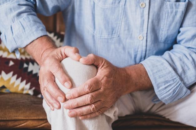 自宅で膝を保持しているソファに座って、膝の問題に直面している年配の老人のクローズアップ。自宅に座ってひざの痛みに苦しんでいる老人