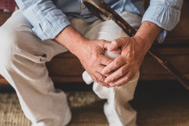 自宅で膝を保持しているソファに座って、膝の問題に直面している年配の老人のクローズアップ。リビングルームで杖を持って座っているひざの痛みに苦しんでいる老人。