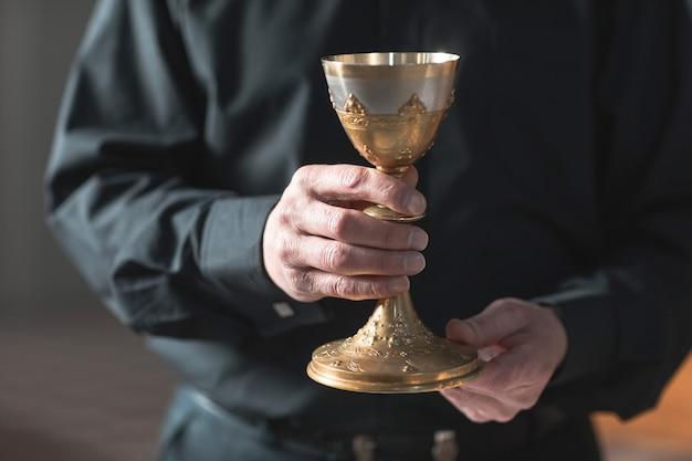 教会でカップを保持している先輩司祭のクローズアップ