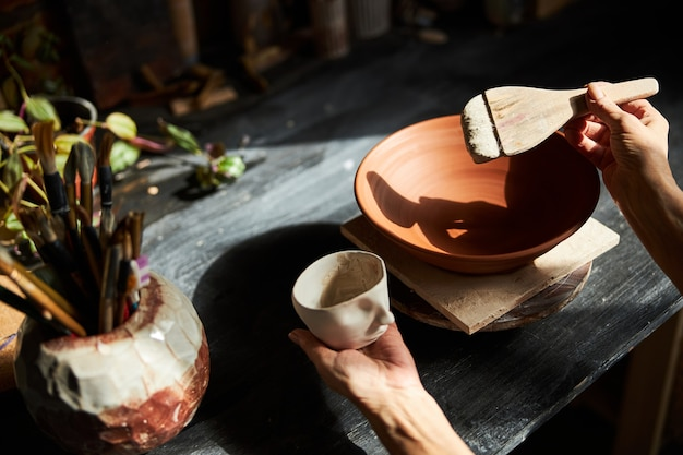 도자기 스튜디오에서 테이블에 앉아있는 동안 클레이 컵과 페인트 브러시를 들고 수석 여자 도예가의 닫습니다