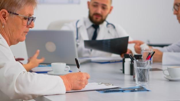 放射線科医の同僚がバックグラウンドでx線の分析とラップトップでの書き込みについて話している間、クリップボードにメモを取っている年配の女性医師のクローズアップ。医療会議を持っているプロのチームワーク