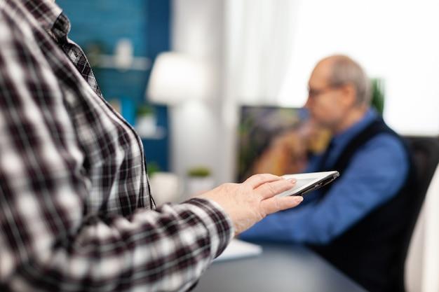 自宅のデジタルデバイスでスクロールする年配の女性の手のクローズアップ。自宅のリビングルームでモダーテクノロイタブレットpcを使用している年配の女性とラップトップコンピューターで作業している夫のクローズアップ。