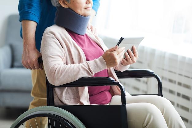 車椅子に座ってデジタルタブレットを使用して彼女の首に包帯で年配の女性のクローズアップ
