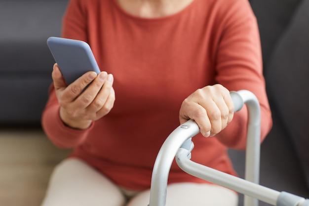 Крупный план пожилой женщины, читающей сообщение на мобильном телефоне дома