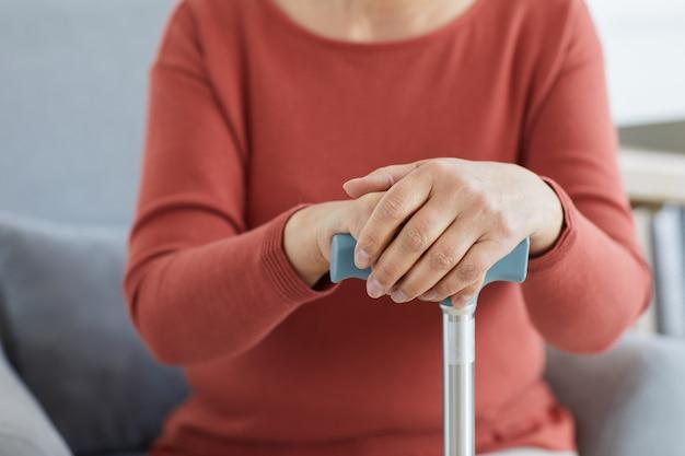 ソファに座って松葉杖を持っている年配の女性のクローズアップ